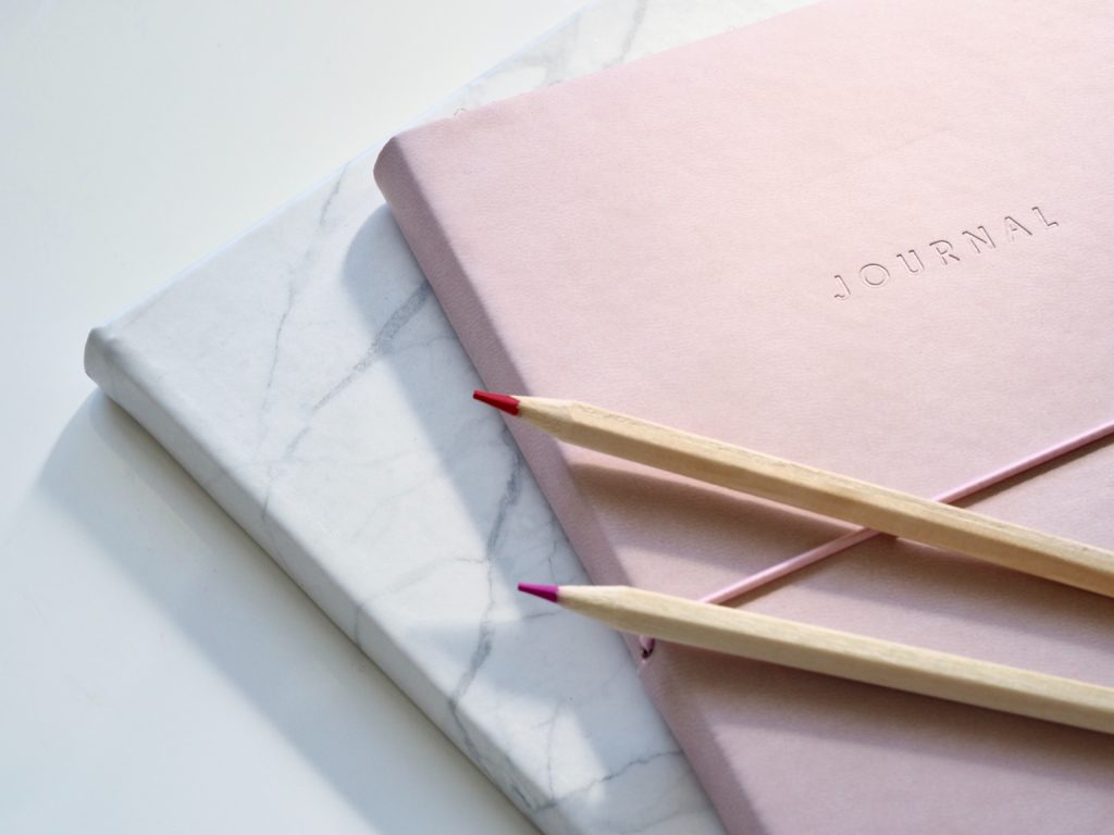 Two journals placed on top of each other, with some pencils on top