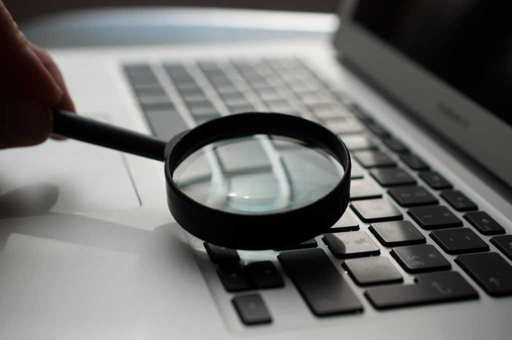 Image of a magnifying glass and laptop for Google Ad Grants post.